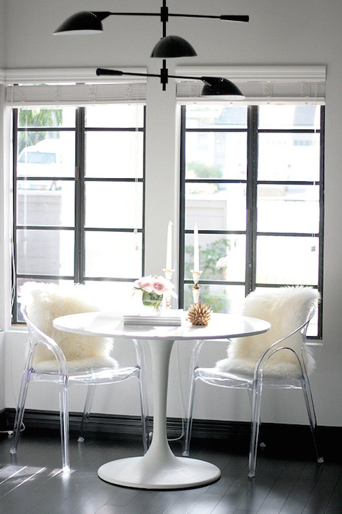 small shop studio chic breakfast nook features table paired acrylic chairs accented sheepskin pelts atop dark floors situated front kitchen kit