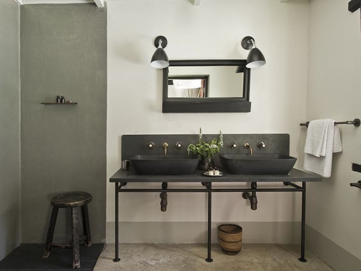 Industrial Style Bathroom With Gray Tadelakt Shower Surround Over Dark Gray  Tadelakt Tiled Shower Floors Topped With A Distressed Black Stool.