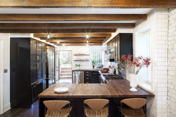Amazing Kitchen With Glossy Black Cabinets Accented With Brass Hardware  Paired With Butcher Block Countertops And Subway Tiled Backsplash.