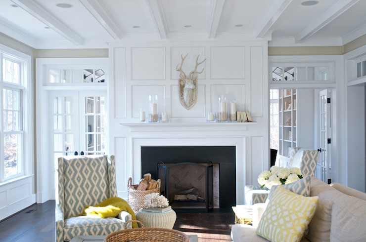 Gorgeous living room with paneled fireplace accented with candles and a faux taxidermy deer mount with transom windows flanked by French doors with transom windows.