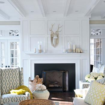 Bookshelves fill nooks on either side of fireplace design for French doors with windows either side