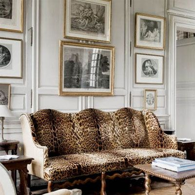 Traditional Living Room With Gilt Framed Antique Black And White Prints  Against A Backdrop Of Full Wall Wainscoting Over An Antique Leopard Print  Sofa.