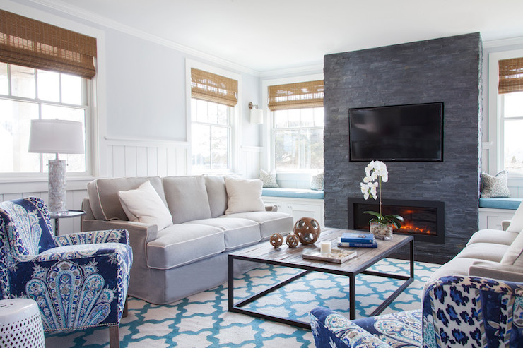 Amazing living room features built-in window seats dressed in turquoise cushions flanking floor to ceiling grey stone fireplace accented with flatscreen TV niche.