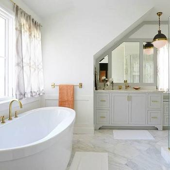Gray And Gold Bathroom With Bathtub Under Sloped Ceiling