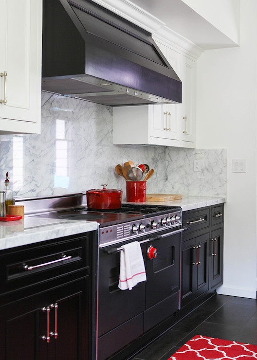 black range hood over black stove alongside red kitchen accents