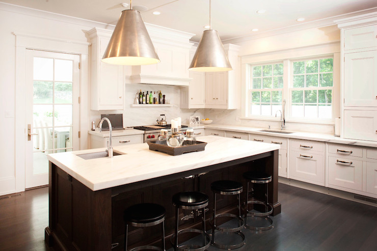 kitchen features white perimeter cabinets paired with calcutta marble
