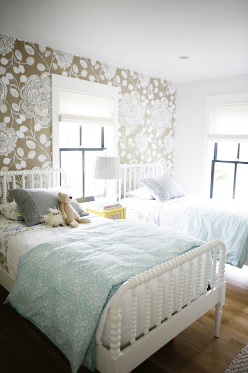 adorable shared kids room features white taupe floral wallpaper accent wall framing pair twin jenny beds dressed gray fringed lind spindle bed queen style king