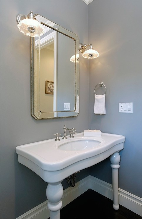 White And Grey Powder Room Features Antiqued Beveled Mirror On Gray Wall  Flanked By Vintage Sconces Over Parisian Pedestal Sink.