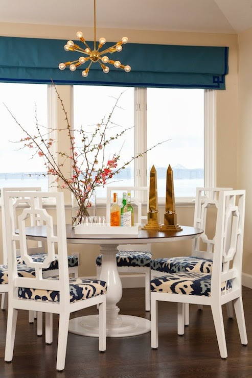 Chic Dining Room With Picture Window Dressed In A Peacock Blue Roman Shade Greek Key Trim Alongside Tan Colored Walls Which Frame The Round White