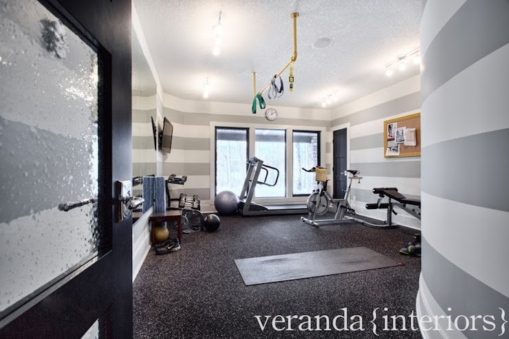 home gym lighting. fabulous home gym with seeded glass black door opening to reveal gray and white horizontal striped walls track lighting illuminating a variety of t