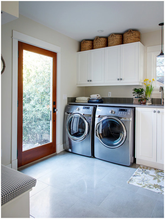 Lovely Laundry Room Features Baskets Atop White Cabinets Suspended Over  Silver, Front Load Washer And Dryer Tucked Under Gray Quartz Countertop  Atop ...