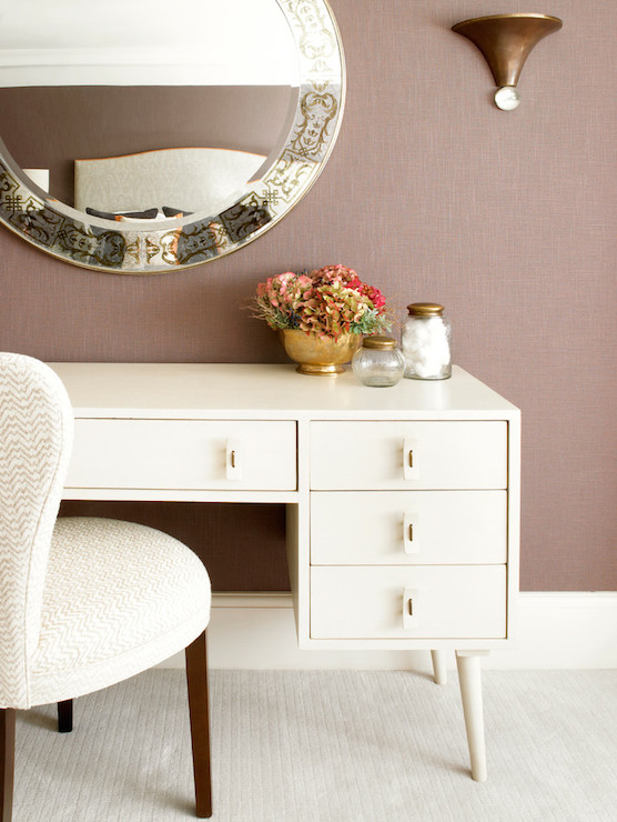 with mauve grasscloth wallpaper a round venetian mirror lit by a copper wall sconce above a midcentury modern white dressing table lined