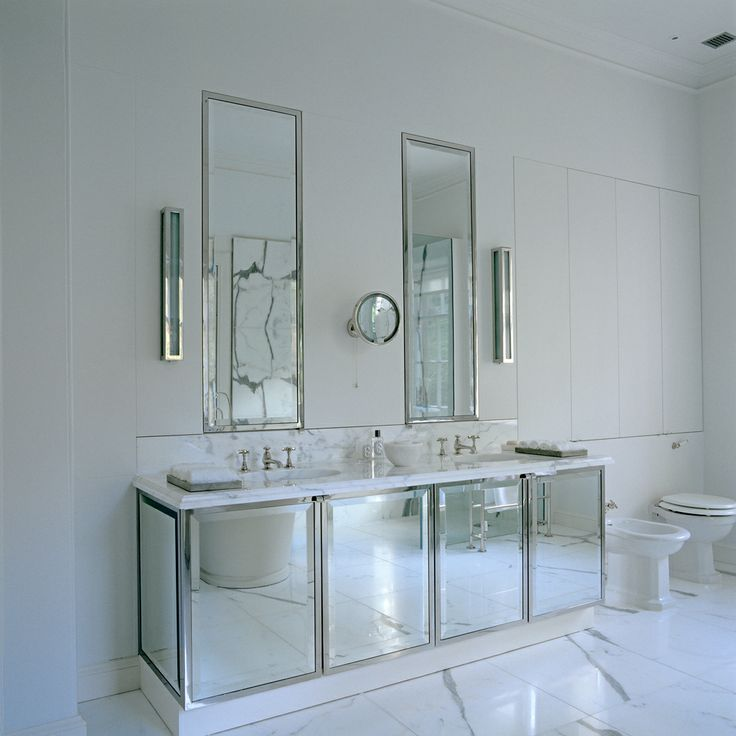 Sleek Bathroom Features Polished Nickel Inset Mirrors Flanked By Long Sconces Over Mirrored Double Vanity Topped With White Marble Atop