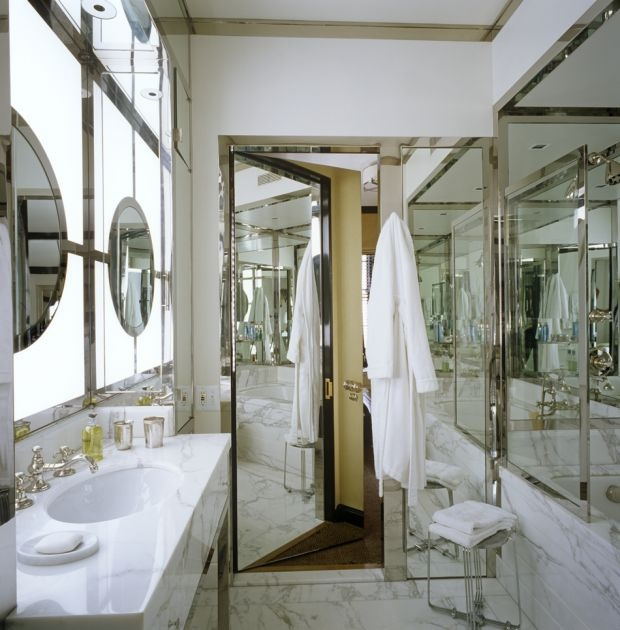 Mirrored Door Opens To Stunning Bathroom Features Round Mirror In Front Of Window Over Polished Chrome Washstand Topped With White Marble Atop