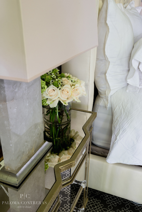 elegant bedroom with a gold mirrored nightstand with crystal pulls topped with crescent table lamps and fresh cut flowers alongside an ivory upholstered