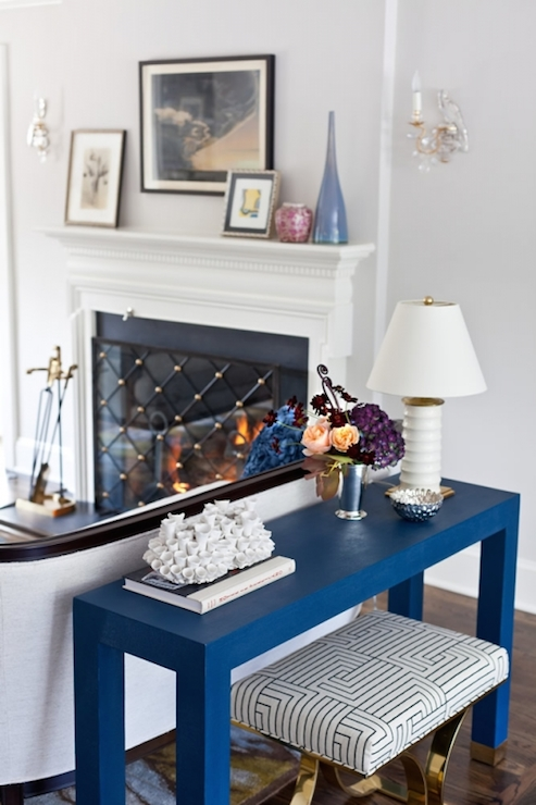 Chic Living Room With Brass X Based Stool Accented Black And White Geometric Cushion Tucked Under Blue Console Table Backing Sofa