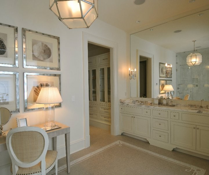 lantern in polished nickel and frosted glass illuminating a collection of beach art in mirrored picture frames over taupe desk topped with clear glass