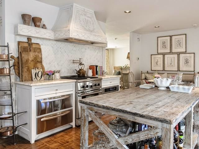 french country kitchen tile backsplash. french country kitchen with white cabinets highlighting a distressed style hood flanked by matching ledges over pot filler on diamond laid marble tile backsplash t