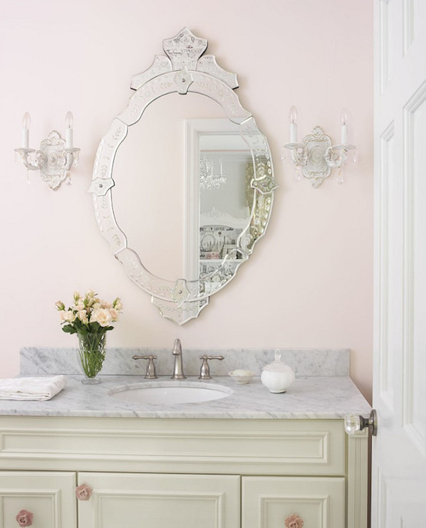 Shabby chic bathroom boasts oval Venetian mirror on soft pink walls  illuminated by shabby chic sconces over cream vanity accented with pink  rosette hardware. Shabby Chic Bathrooms Design Ideas