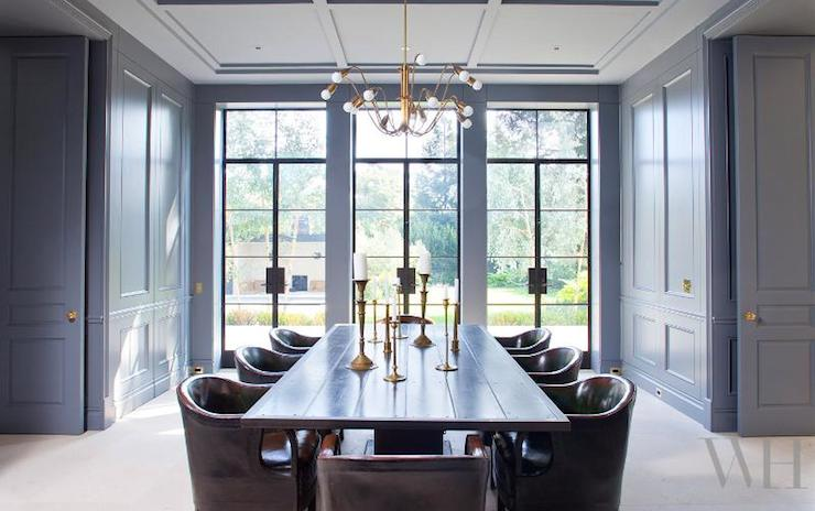 Amazing Dining Room Features Gray Paneled Ceiling Accented With Brass Chandelier Over Planked Table Surrounded By Brown Leather Chairs Placed