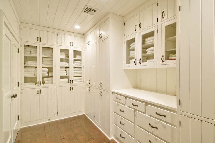 Linen closet features tongue and groove ceiling over floor to ceiling  built-in cabinets with beadboard doors adjacent to glass-front
