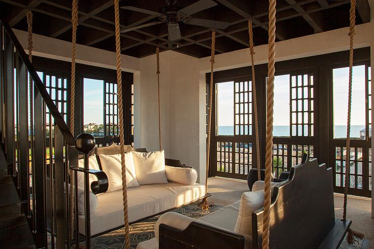 lounge features hanging sofas suspended from ropes facing each other atop gray moroccan rug surrounded by sliding lattice doors leading to