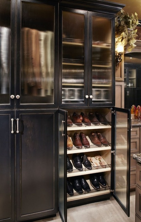 Charming Walk In Closet Features Stacked Black Cabinets Accented With Glass Doors  Filled With Rows And Rows Of Slanted Shoe Shelves.