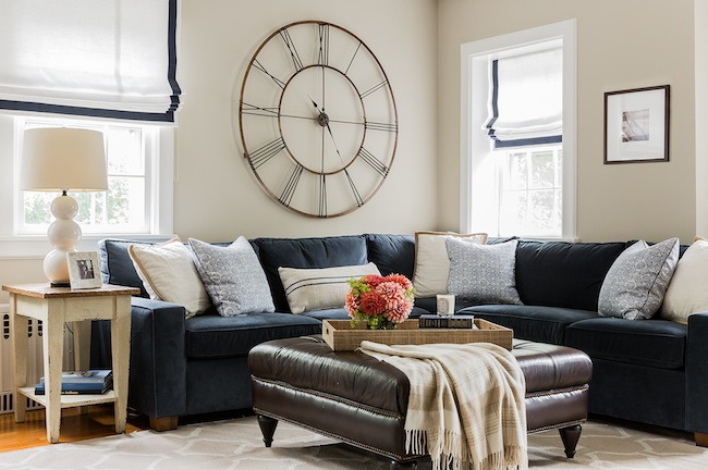 Wonderful Living Room Features French Clock Over Navy Velvet Sectional Sofa  Adorned With Beige Piped Pillows And Blue Print Pillows Placed Under  Windows ... Part 58