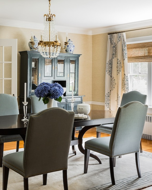 Sophisticated Dining Room Features Gold Grasscloth Wallpaper Accented With Chair Rail Framing Window Dressed In Linen Medallion Curtains Layered Over Bamboo
