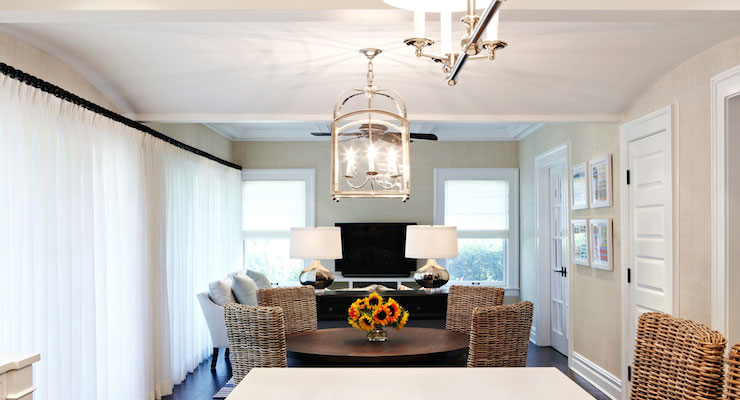 Long Living And Dining Space Features A Small Arch Top Lantern Illuminating Pedestal Table Surrounded By Wicker Chairs Placed In Front Of