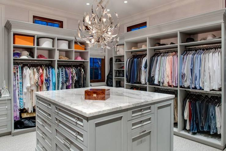 Walk In Closet With Open Cubbies Over Clothes Rails Centered On A Gray Island Accented Crystal Pulls And White Marble Counter Illuminated By