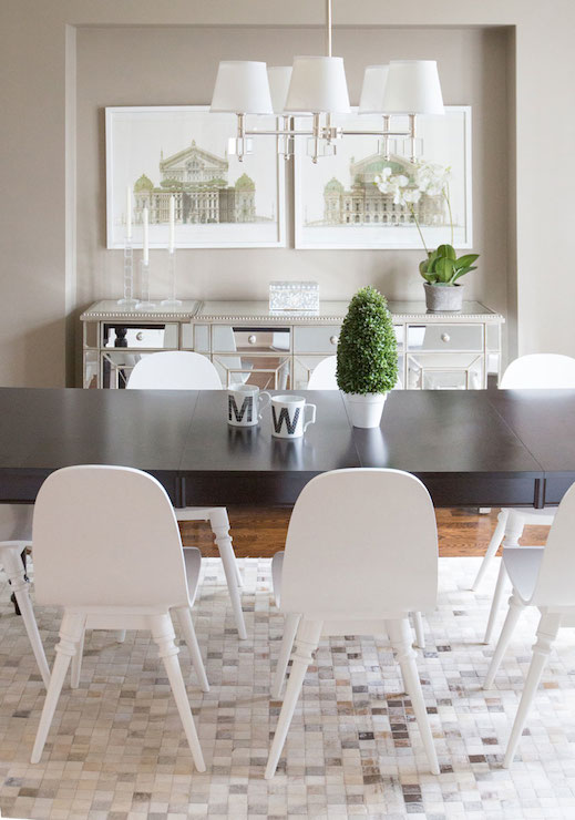 Neutral Dining Room Features Long Espresso Table Lined With Modern White Chairs Atop Mosaic Hairhide Rug Illuminated By Polished Nickel And