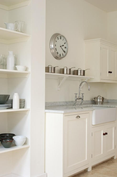Medium image of simple white cottage kitchen featuring a brushed nickel wall clock over a single white shelf holding pots above a farm kitchen sink paired with a bridge