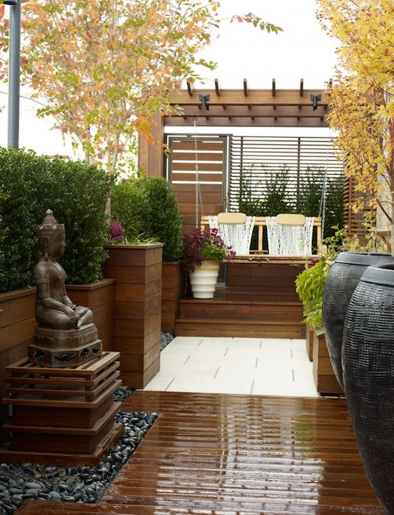 Zen Rooftop Garden Boasts A Buddha Water Fountain Laid Out In River Rocks  Facing Large Black Jars Beside Pergola.