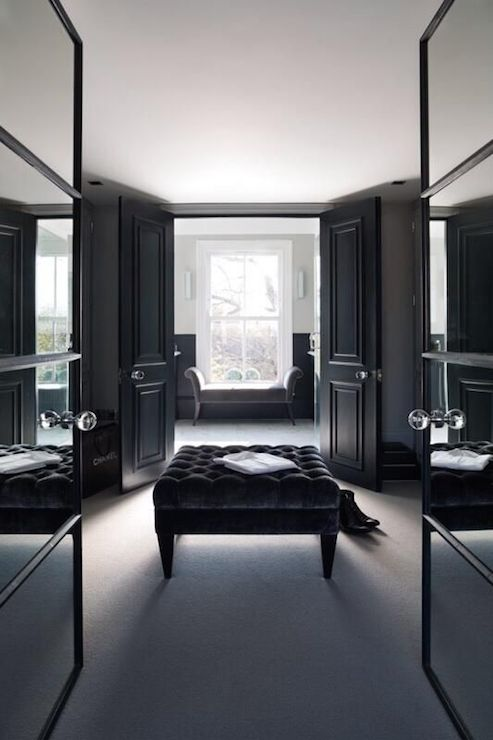 glass double doors open to sleek black closet boasting black black velvet tufted ottoman placed dead center of the space which also leads to black double