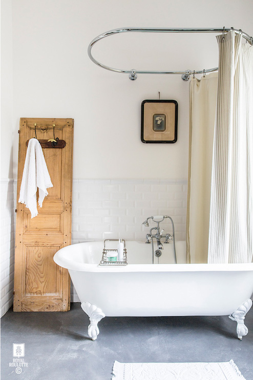 Vintage Bathroom Boasts Upper Walls Painted Soft White And Lower Clad In Beveled Subway Tiled Wainscoting With Oval Shower Rail Mounted On Wall