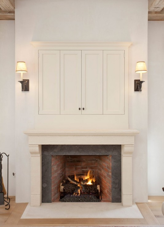 country living room features a limestone fireplace with charcoal gray surround under a concealed tv hidden behind folding doors illuminated by oilrubbed
