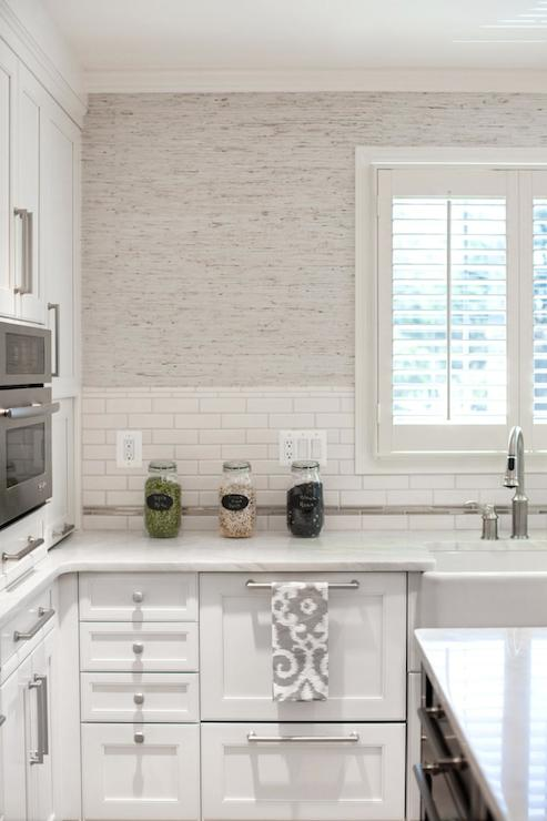 Stunning Kitchen Features White Shaker Cabinets Paired With Luminous Calacatta Marble And A White Linear Tiled Backsplash Under Light Gray Grasscloth