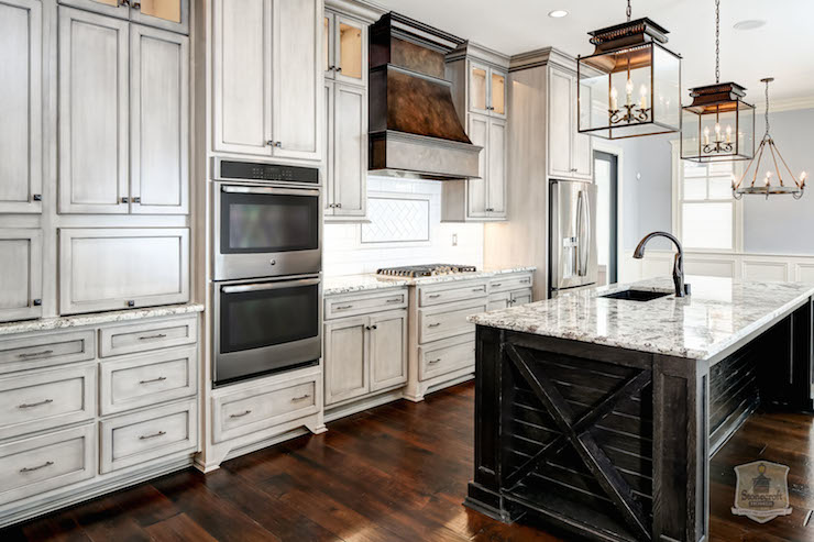 Fabulous kitchen features weathered gray cabinets paired with oil
