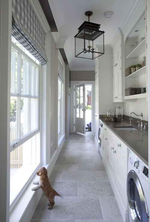 Fabulous Laundry Room Features A Honore Hanging Lantern Illuminating Crisp White Cabinets Flanked By Front Load Washer And Dryer Topped With Gray Quartz