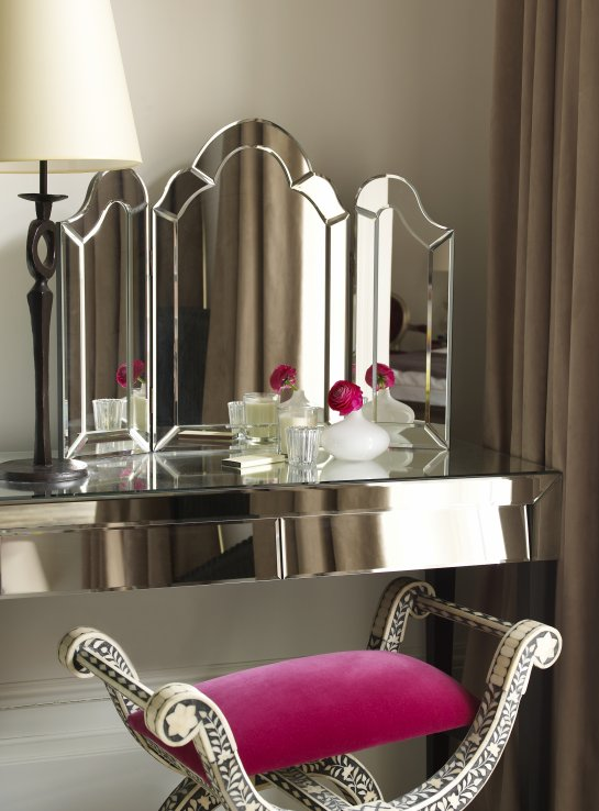 light tan walls and taupe drapes frame a mirrored dressing table with arched folding vanity mirror and iron table lamp paired with a bone inlaid vanity
