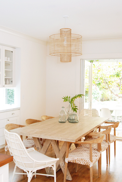 Stunning Dining Room Features An X Based Dining Table Lined With Foxed Oak  Armchairs And Modern White Rattan Host Chairs Below An Anthropologie Deco  Rattan ...