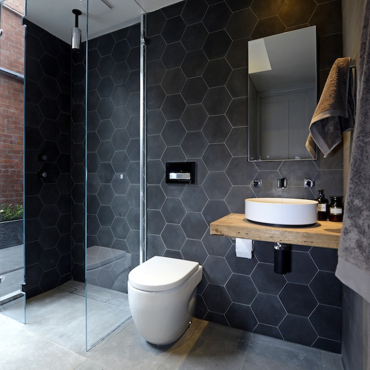 modern bathroom features a black slate hexagonal tiled accent wall