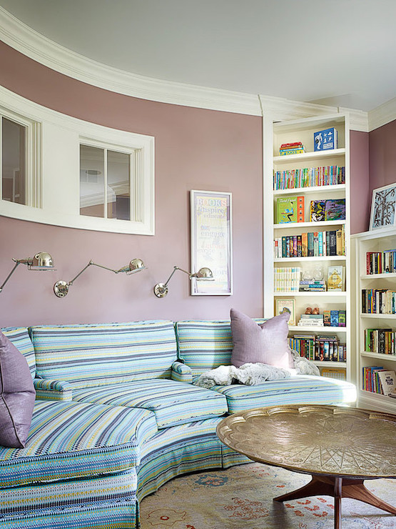 Framing Small Windows Over A Curved Striped Sofa Adorned With Lavender Pillows Illuminated By Three Polished Nickel Swing Arm Sconces Facing Moroccan