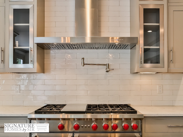 Close Up Shot Of Light Gray Colored Kitchen Cabinets Framing Wolf Range Flanked By White Marble Countertops Alongside An Elongated Glazed Tile Backsplash