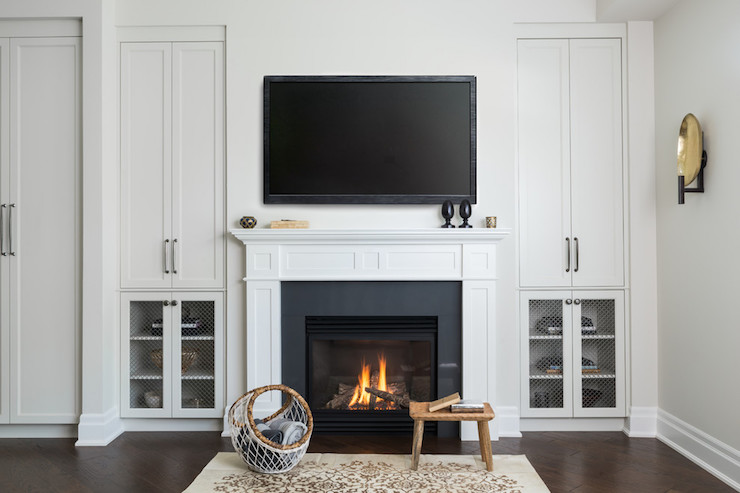 Living room boasts a flatscreen TV over a traditional fireplace with millwork accented with black surround flanked by alcoves filled with built ins boasting cabinets with chicken wire doors.