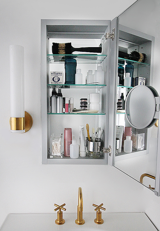 1 door 3 drawers topped with white glossy countertop framing round sink and kohler purist faucet in vibrant moderne brushed gold under kohler verdera h