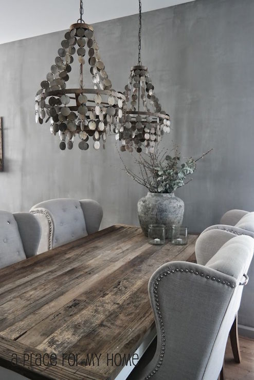 wood dining table lined with gray wingback tufted dining chairs