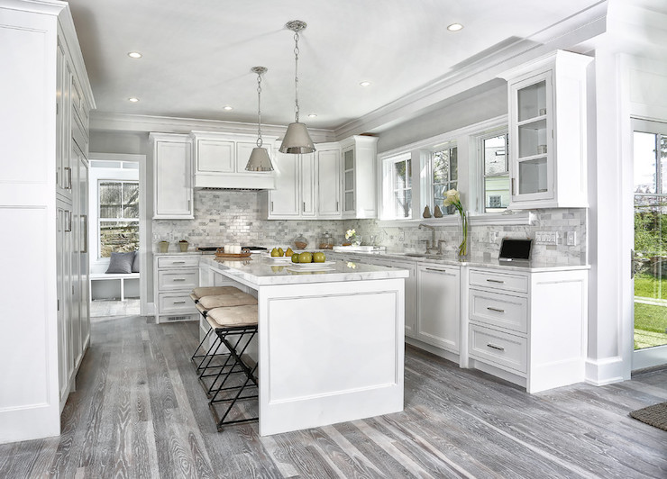 Gorgeous white and gray kitchen boasts a long center island with