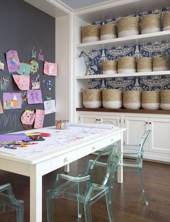 Amazing Kidsu0027 Playroom Boasts A Chalkboard Accent Wall Placed In Front Of A  White Play Table With Drawers Lined With Kartell Lou Lou Ghost Chairs In  Across ...